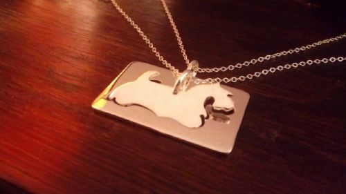 A pair of Scottish terrier dog pendants made from one pierce of sterling silver